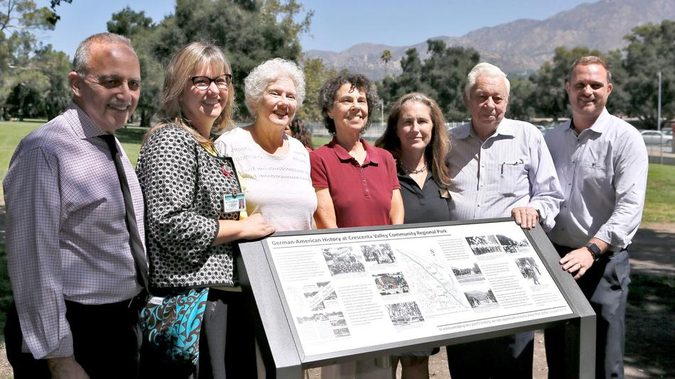 Members of the ad hoc task force for the replacement Hindenburg Park sign, including Mona Field, center, pose after it is unveiled Friday at Crescenta Valley Community Regional Park in La Crescenta on Friday.