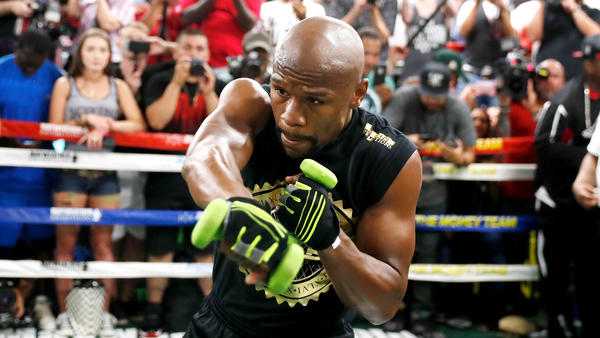 Floyd Mayweather Jr. shadow boxes with weights in his hands during a workout for the media