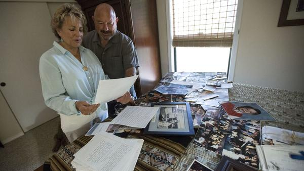 Sharon Holland, left, and husband Carty look over photos and letters written by their son Andrew Hol