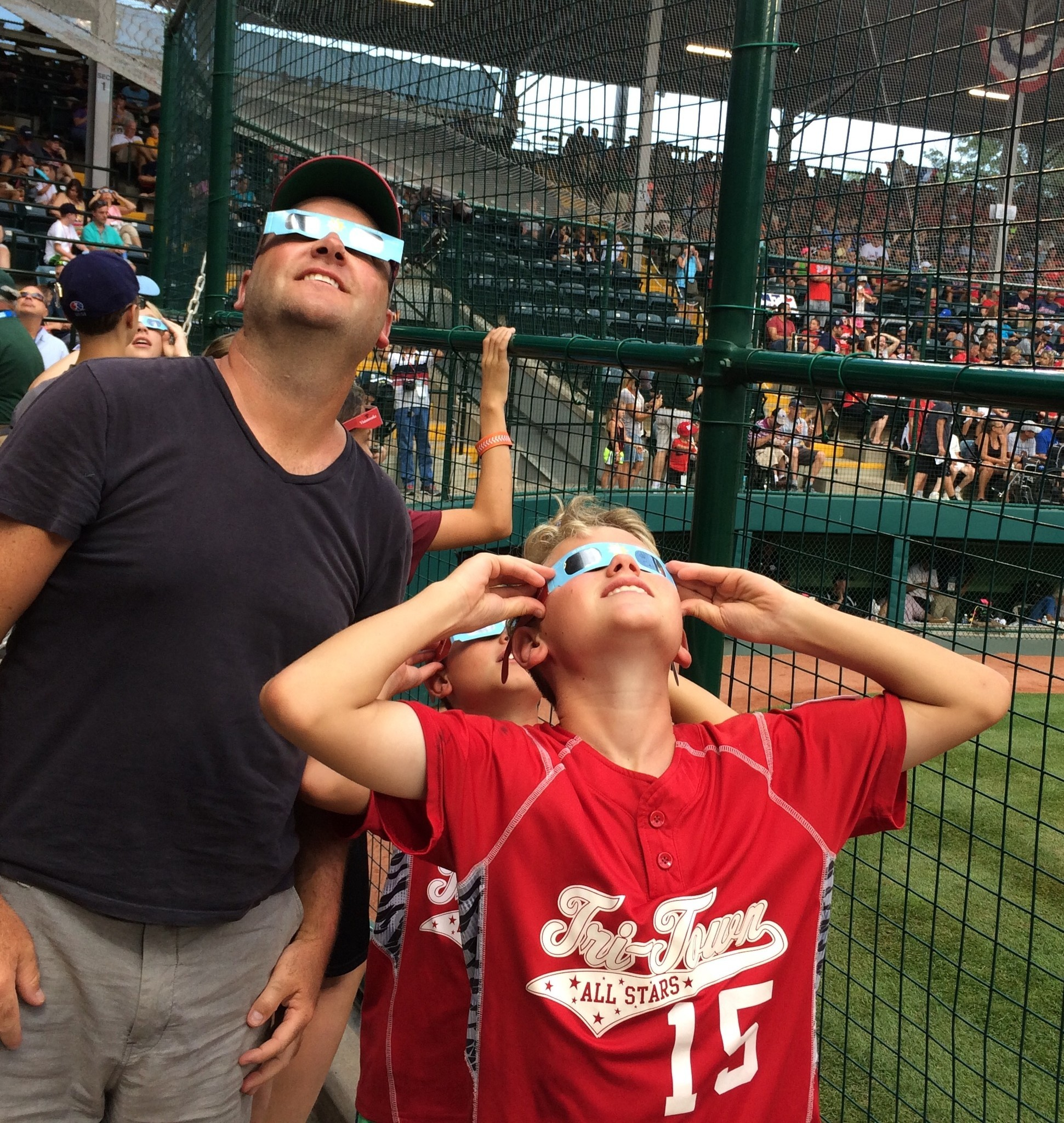 Mike Wenzel and sons Kyke and A.J. of New Jersey check out the solar eclipse between games at the Little League World Series in South Williamsport, Pa. on Monday. (Kevin Baxter / Los Angeles Times)