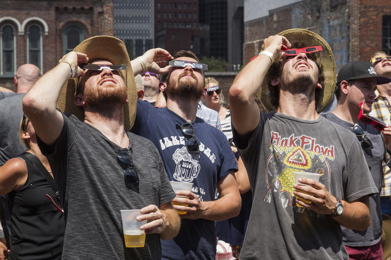 Revelers observe the solar eclipse from the rooftop bar of Nudie's Honkey Tonk in Nashville. (Erik Schelzig / Associated Press)