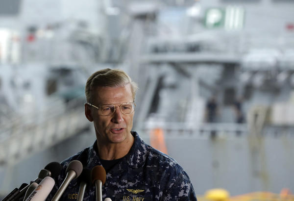 Vice Adm. Joseph Aucoin Commander of the U.S. 7th Fleet speaks during a press conference with damaged USS Fitzgerald as background earlier this year