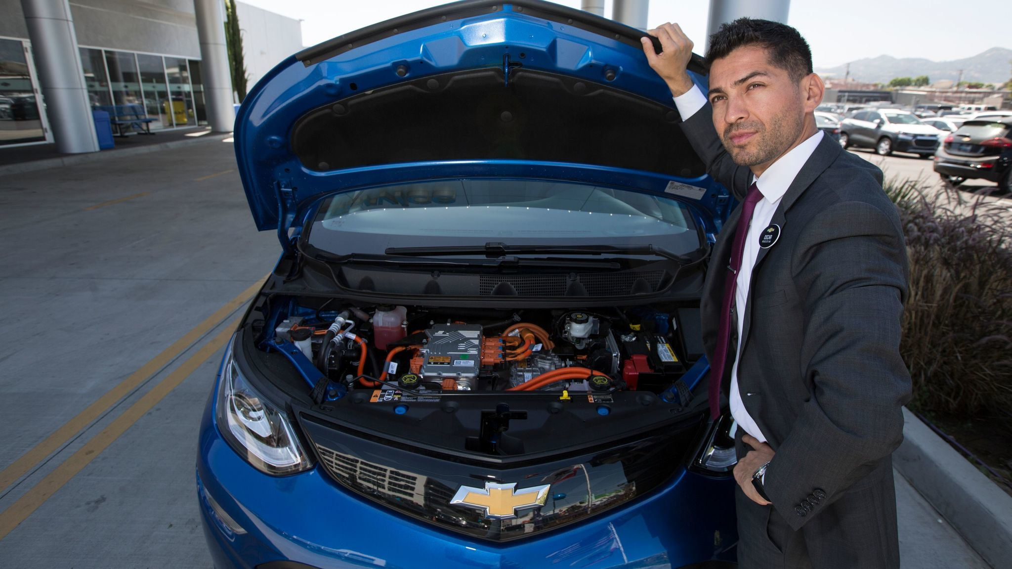 Oscar Gutierrez of Community Chevrolet in Burbank under the hood of a Bolt electric car.
