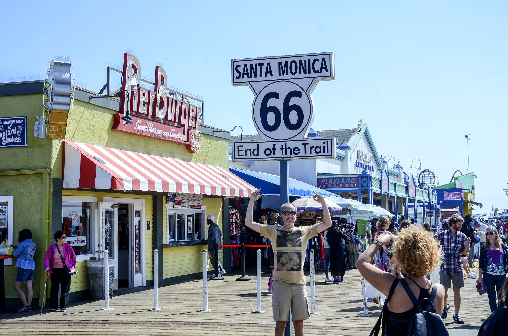 A man poses for a photo in front of the Route 66 sign on Santa Monica Pier.