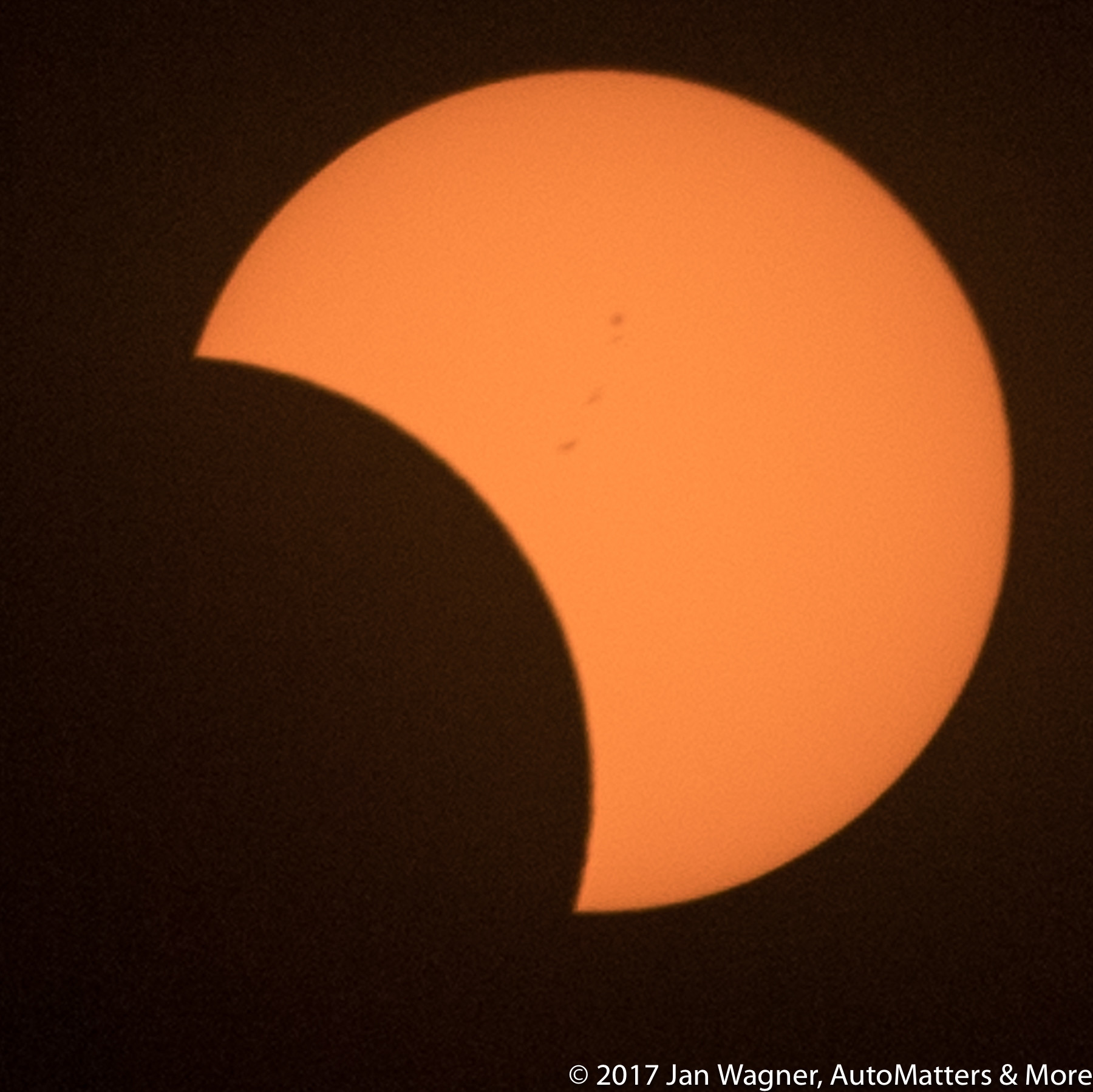 Partial solar eclipse with sunspots