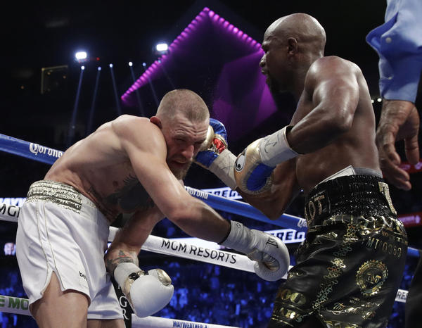 Floyd Mayweather Jr. connects to the head of Conor McGregor during their super-welterweight bout. (Isaac Brekken / Associated Press)