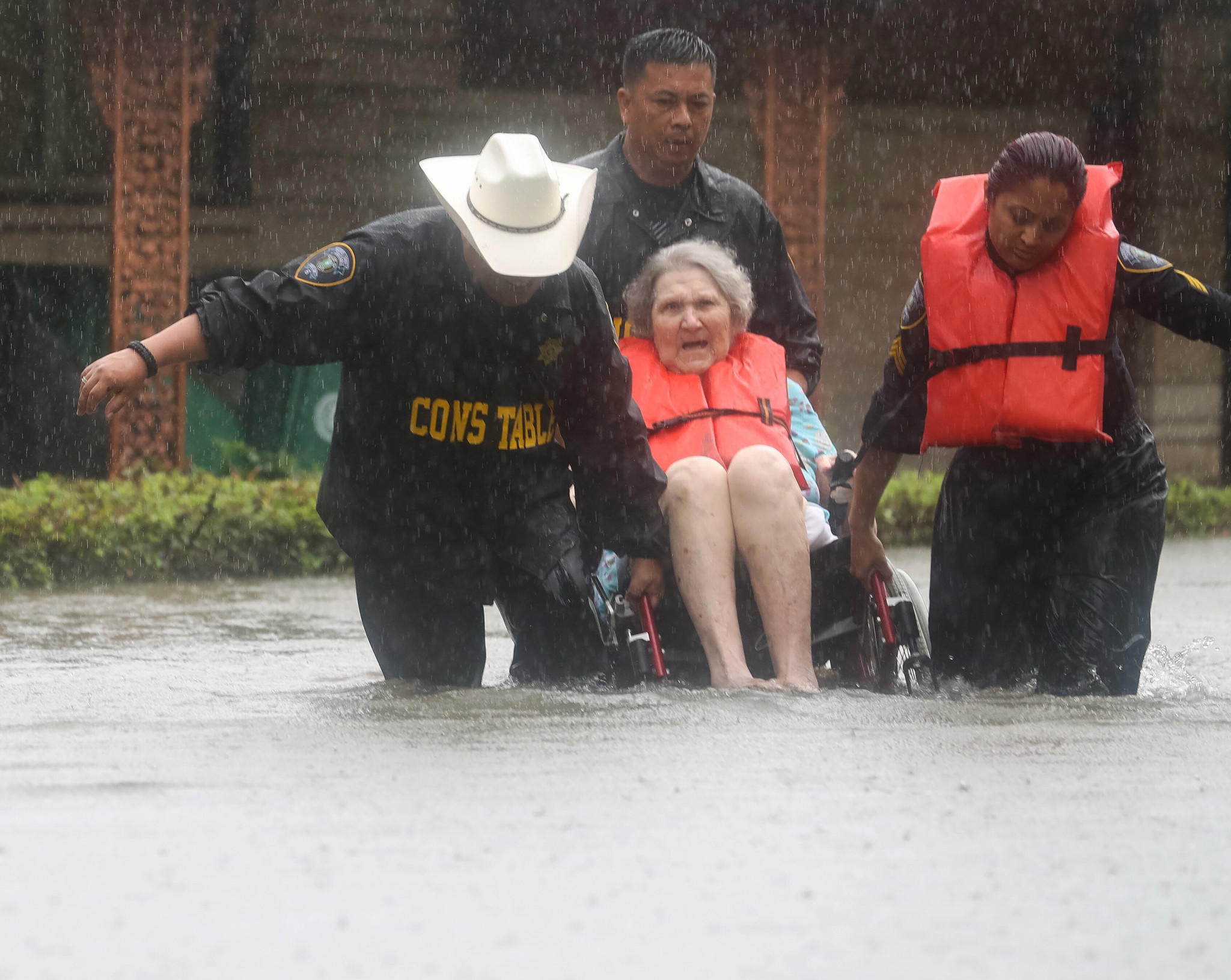 Deputy Constables Sgt. Paul Fernandez, from left, Sgt. Michael Tran and Sgt. Radha Patel rescue a woman from rising water near Brays Bayou after heavy rains on Sunday.