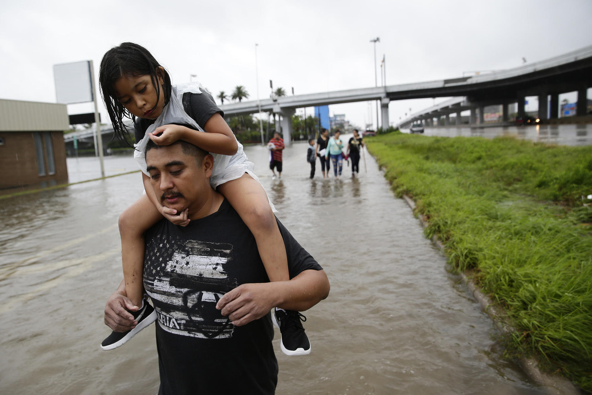 Jesus Nunez carries his daughter Genesis, 6, as he and numerous family members flee their flooded home, walking nearly four hours to the safety of a relative's house on Sunday.
