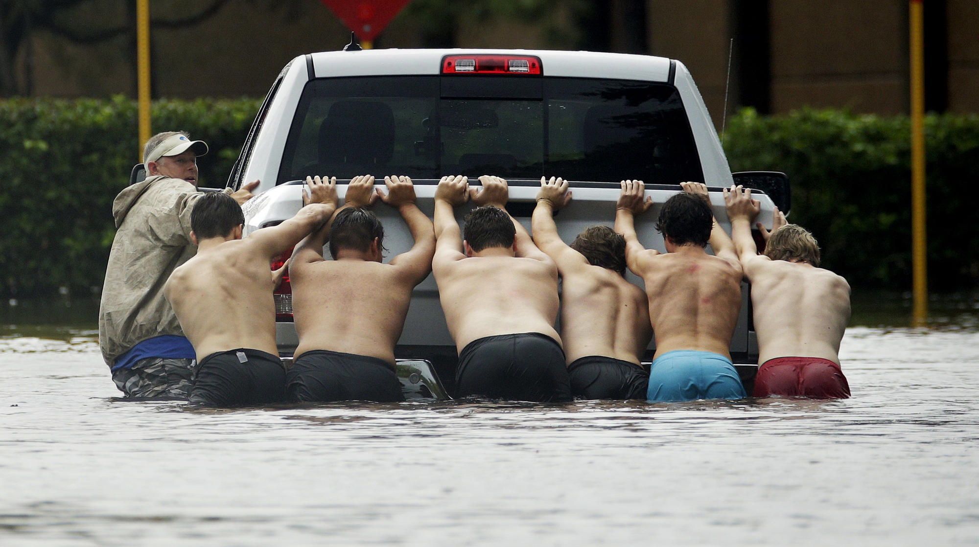 People push a stalled pickup to through a flooded street in Houston on Sunday, as Tropical Storm Harvey dumped heavy rains.