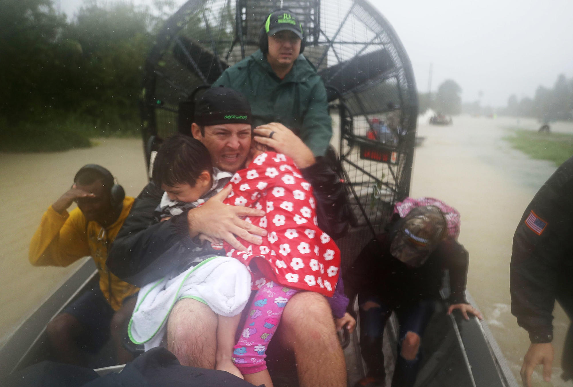 Dean Mize holds children as he and Jason Legnon use an airboat to rescue people from flooded homes in Houston