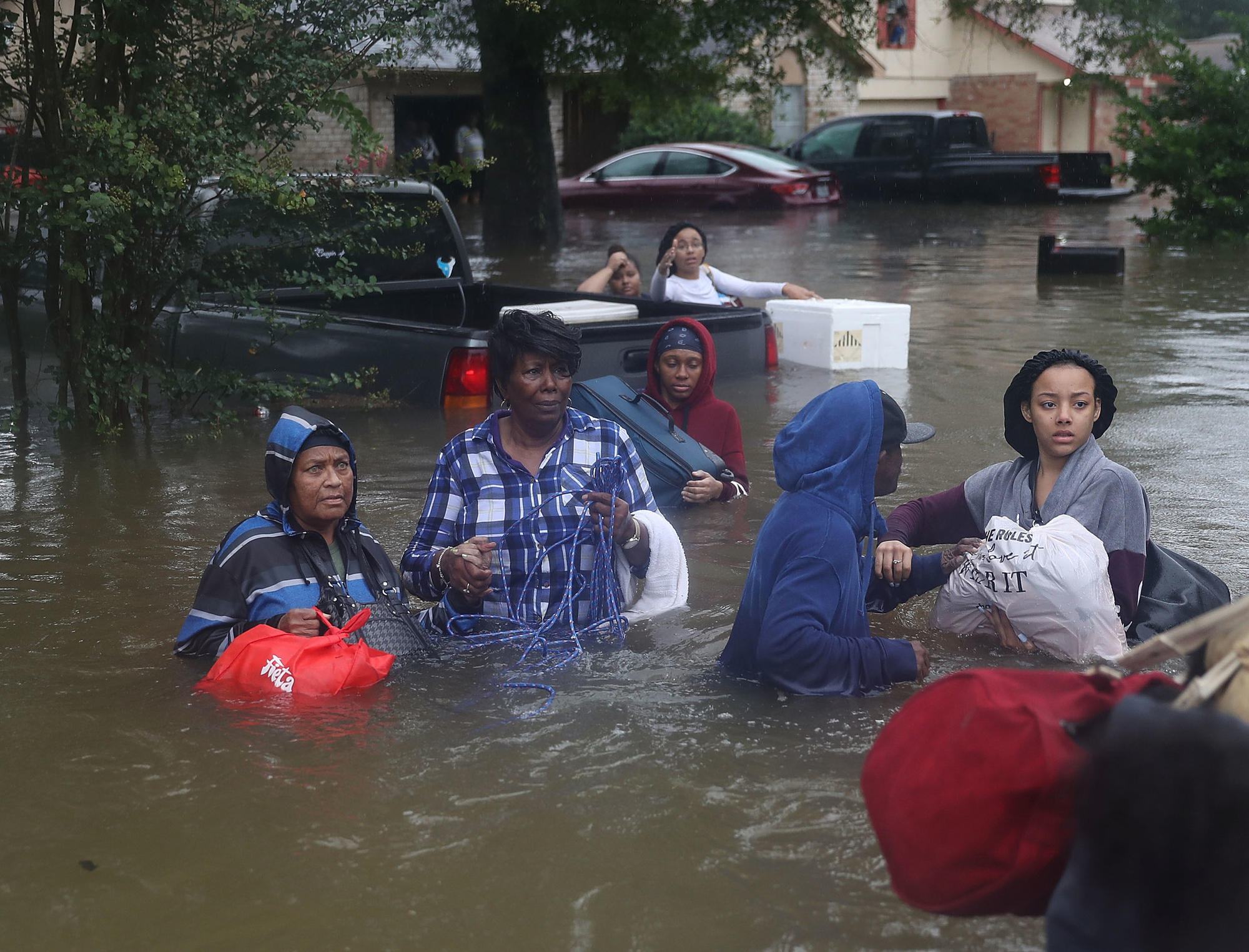 People evacuate their flooded homes on Monday in Houston.