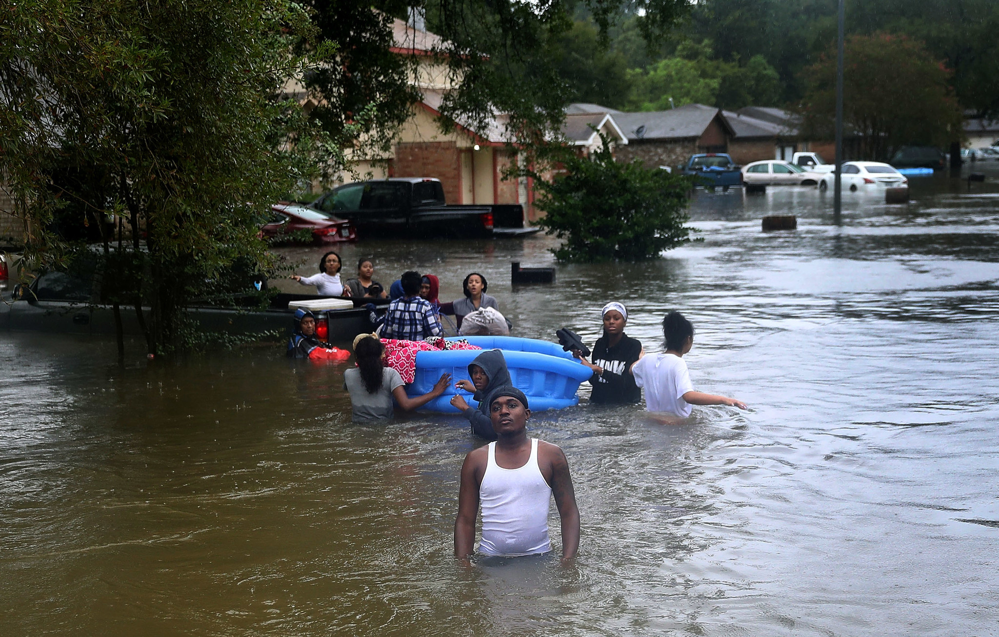 People wade through a flooded street in Houston.