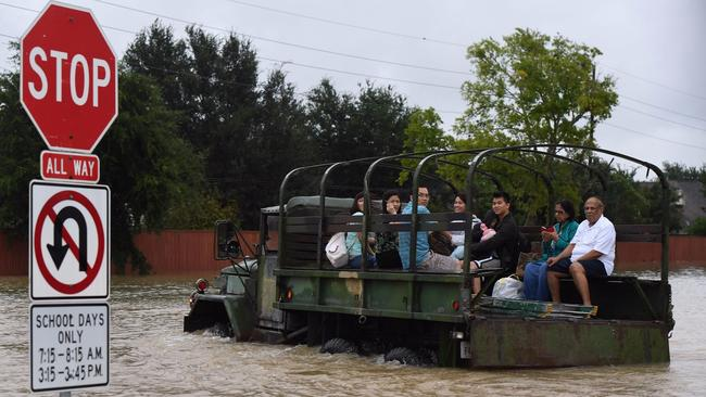 Residents are evacuated by a military vehicle in the Clodine district after Hurricane Harvey caused