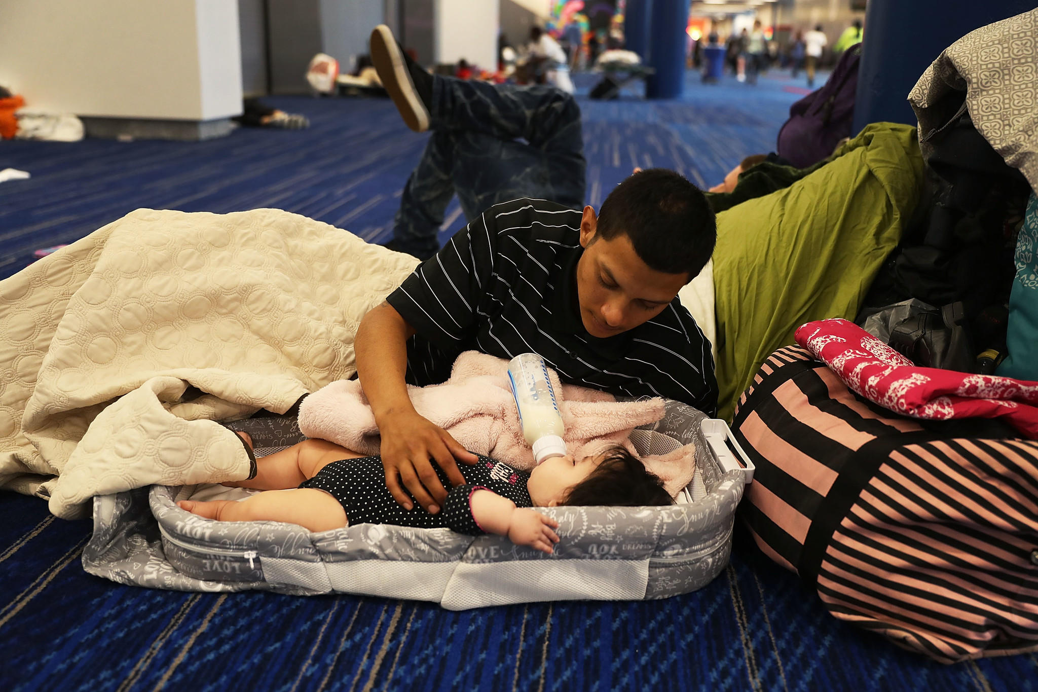 ... Mark Ocosta and his baby, Aubrey, take shelter at the George R. Brown Convention Center. (Joe Raedle / Getty Images)