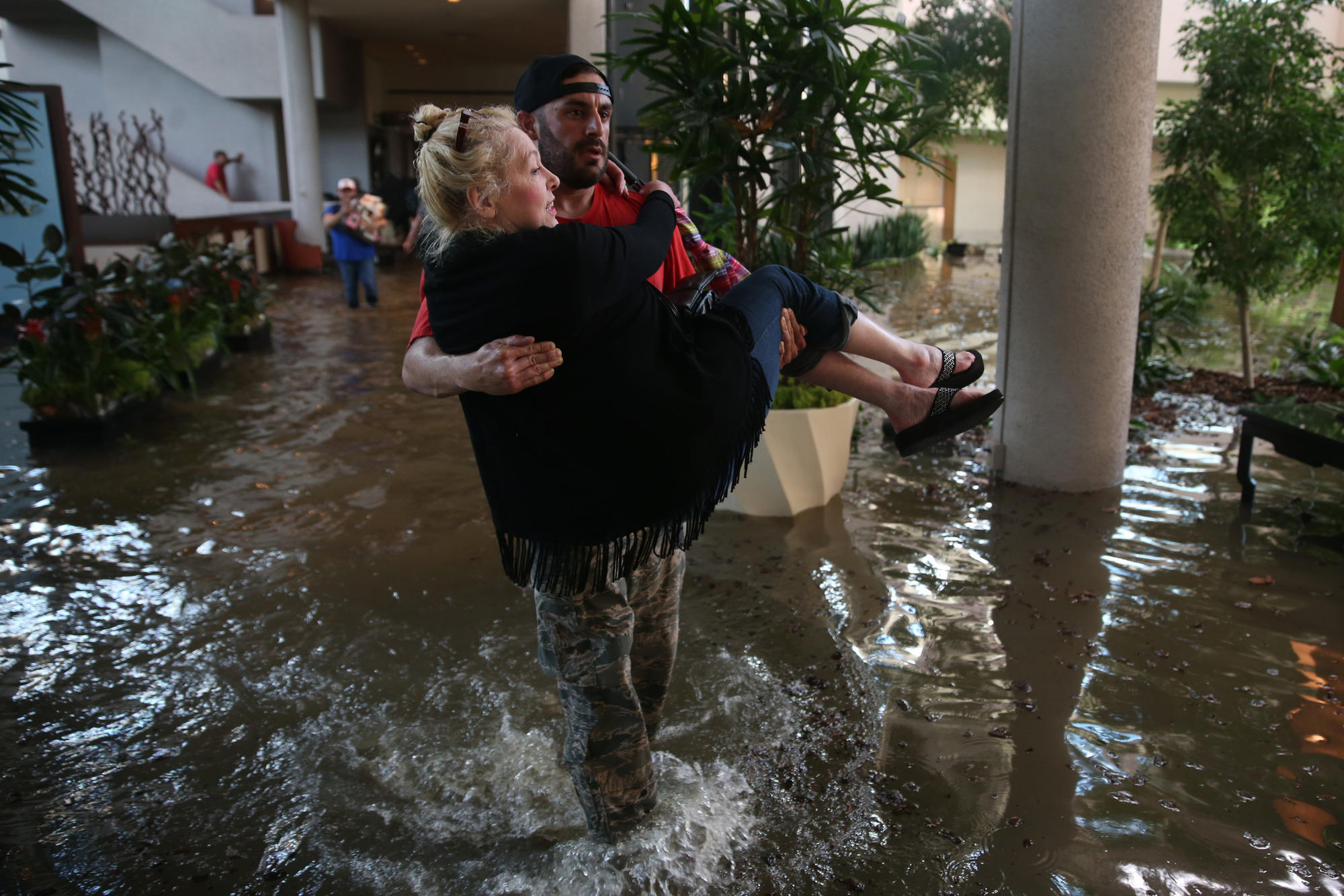 CaroLine Kirkpatrick of Salt Lake City, Utah, is evacuated from the Omni Hotel by rescue worker Adam Caballero in Addicks, a suburb of Houston, Texas.