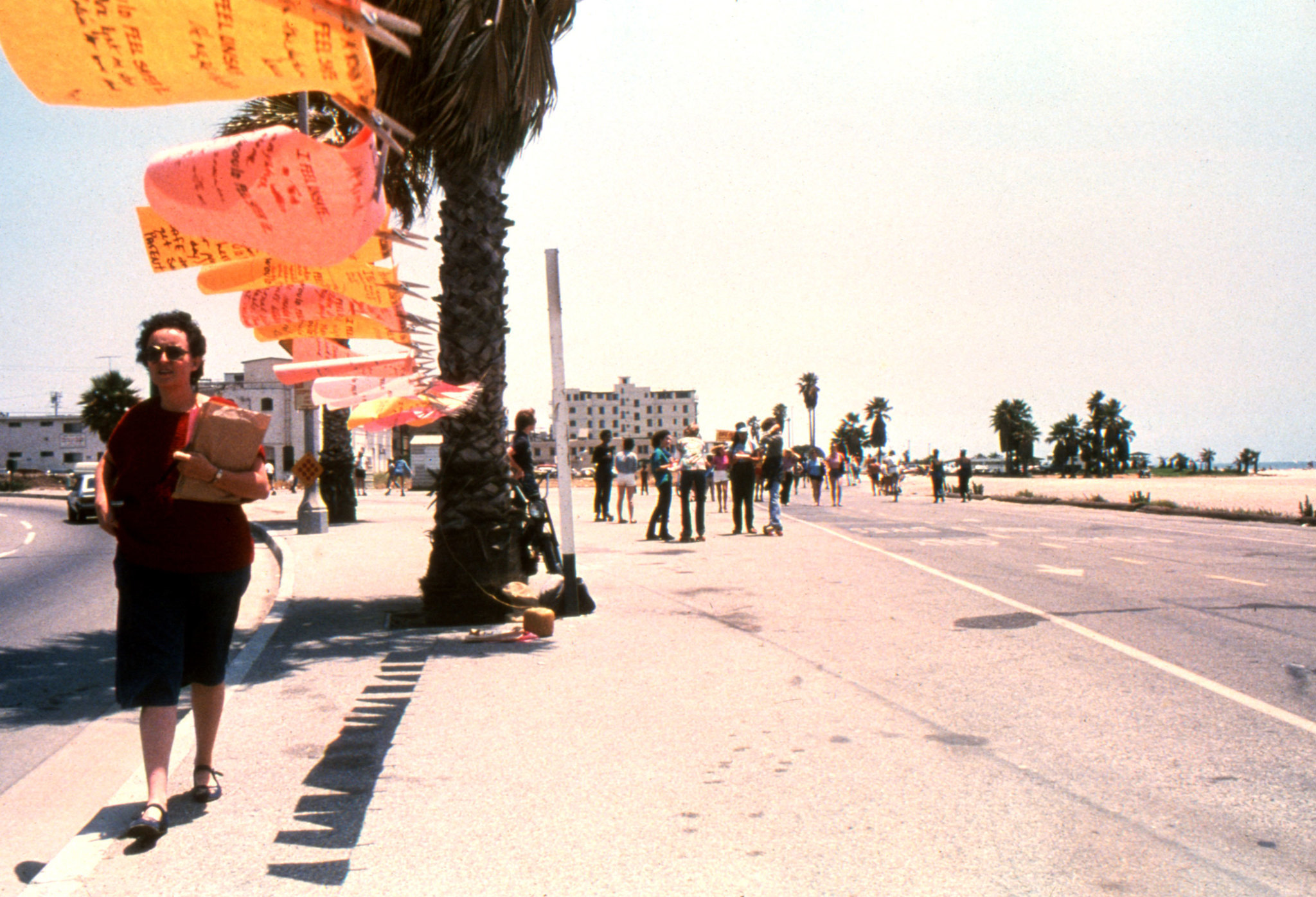 "Mónica Mayer walks along the installation of ""El Tendedero"" in Los Angeles in 1979."