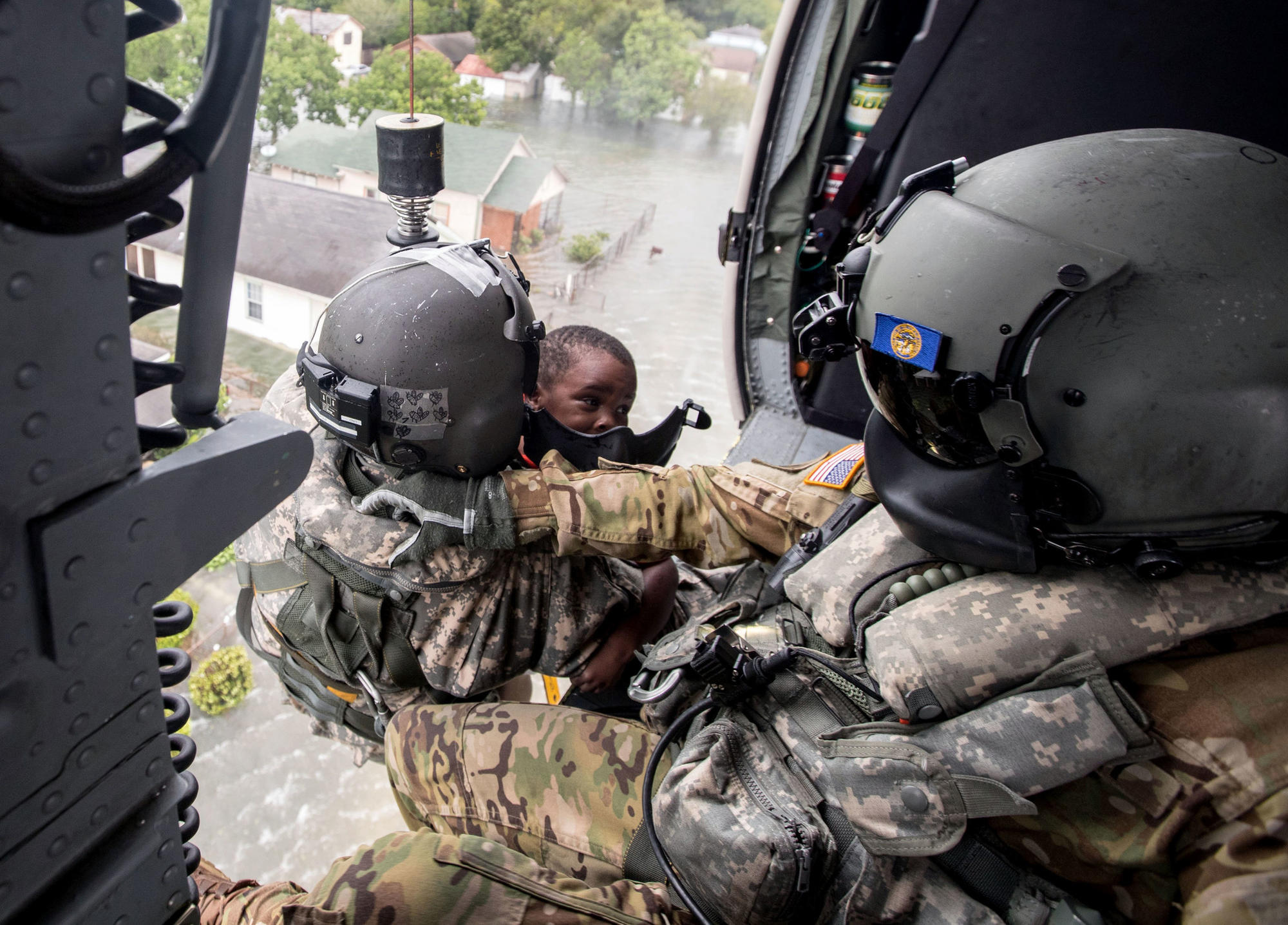 ... Staff Sgt. Lawrence Lind, left, hoists a child into a Black Hawk helicopter