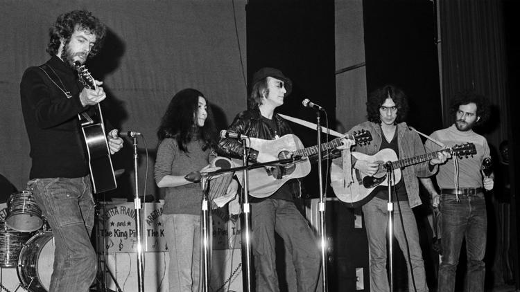 John Lennon and Yoko with Jerry Rubin (far right) playing percussion onstage at the Apollo Theater (Bob Gruen / Fantagraphics Books, Inc.)