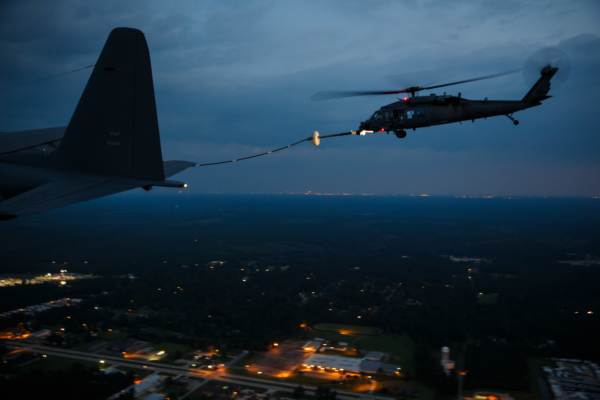 A military search and rescue helicopter refuels mid-flight before resuming nighttime missions over flood areas.