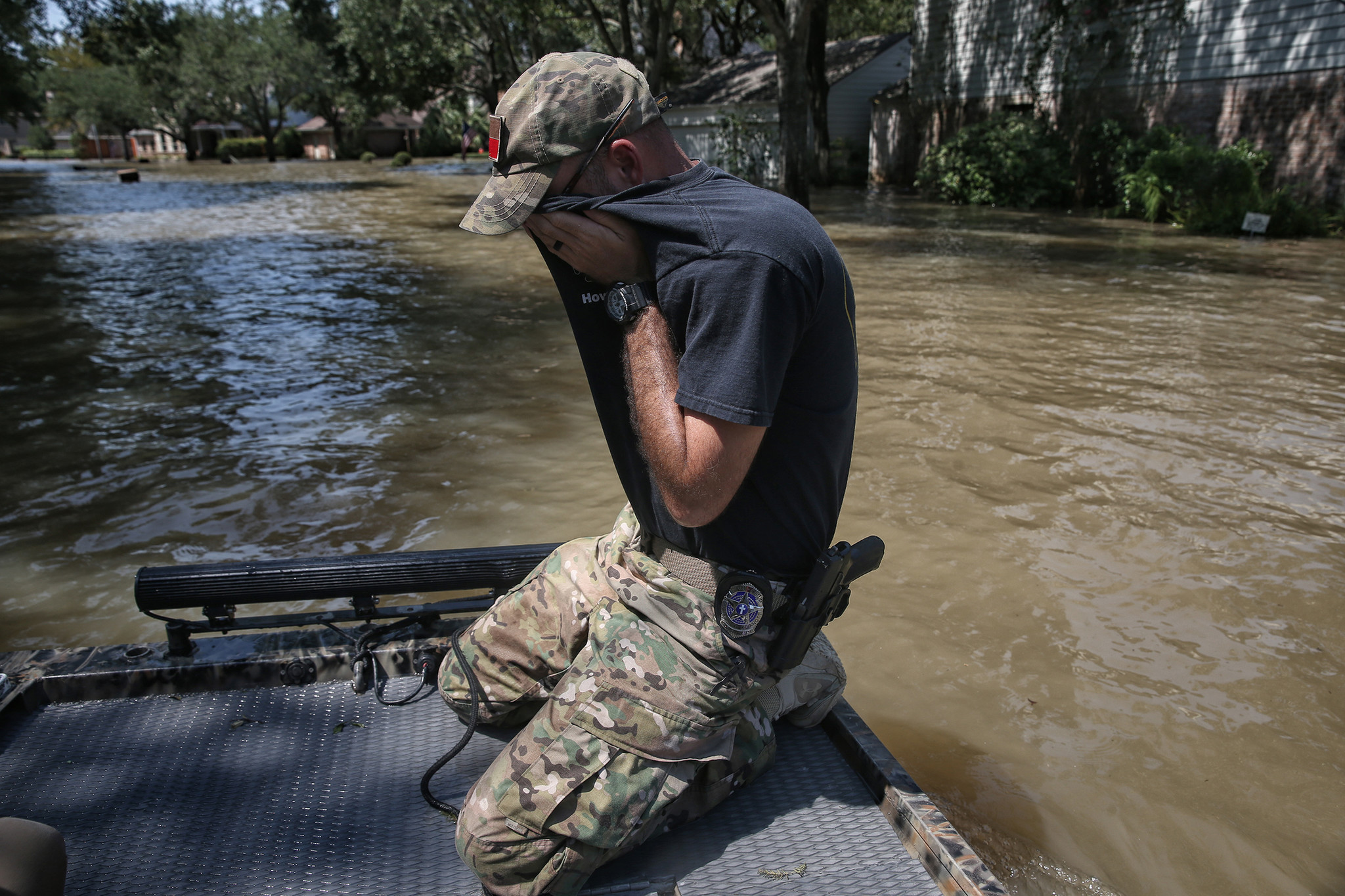 Wes Higgins wipes sweat from his face as he finishes the last of five days of patrolling flooded neighborhoods in his own boat.
