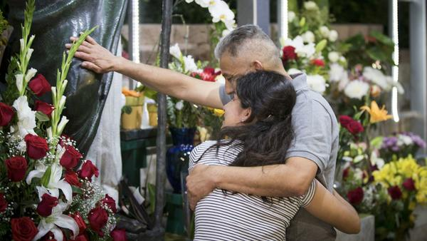 Romulo Avelica Gonzalez hugs his niece, Diana Vargas, as he prays at a shrine to St. Jude the Apostl