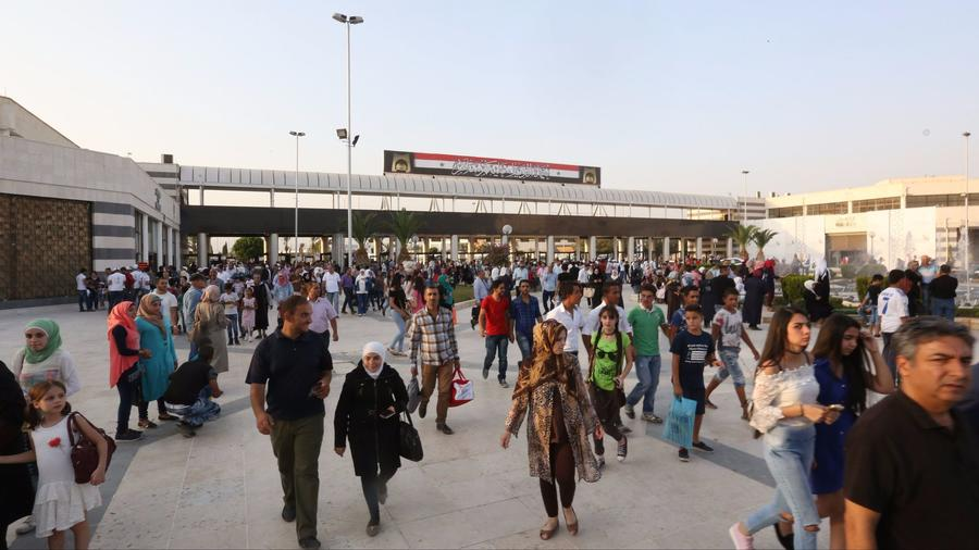 People visit the Damascus International Fair on August 20th. — Photograph: Youssef Badawi/European Pressphoto Agency.