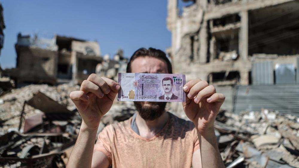 A Syrian man holds up the new 2,000-pound Syrian banknote, featuring the image of President Bashar Assad, in front of damaged buildings in the rebel-held city of Douma on July 9th. — Photograph: Mohammed Badra/European Pressphoto Agency.