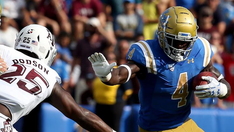 UCLA running back Bolu Olorunfunmi squeezes out extra yardage against Texas A&M on Sept. 3. (Luis Sinco / Los Angeles Times)