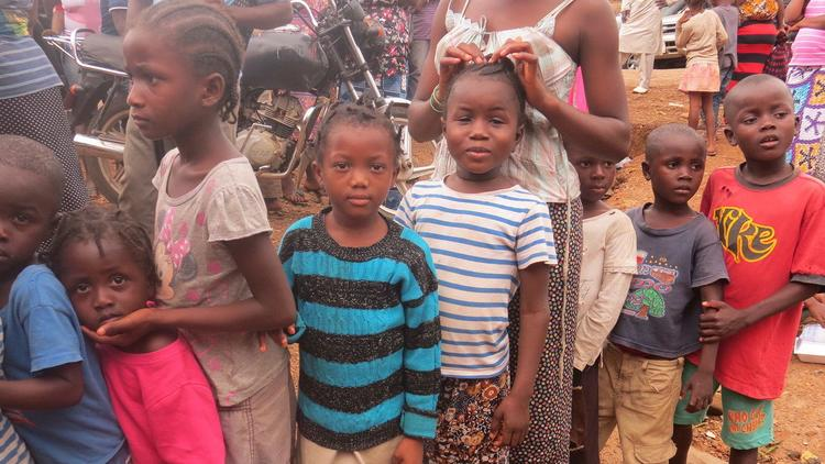In this Aug. 19 photo, children displaced by floods and mudslides wait for food ration in Freetown,