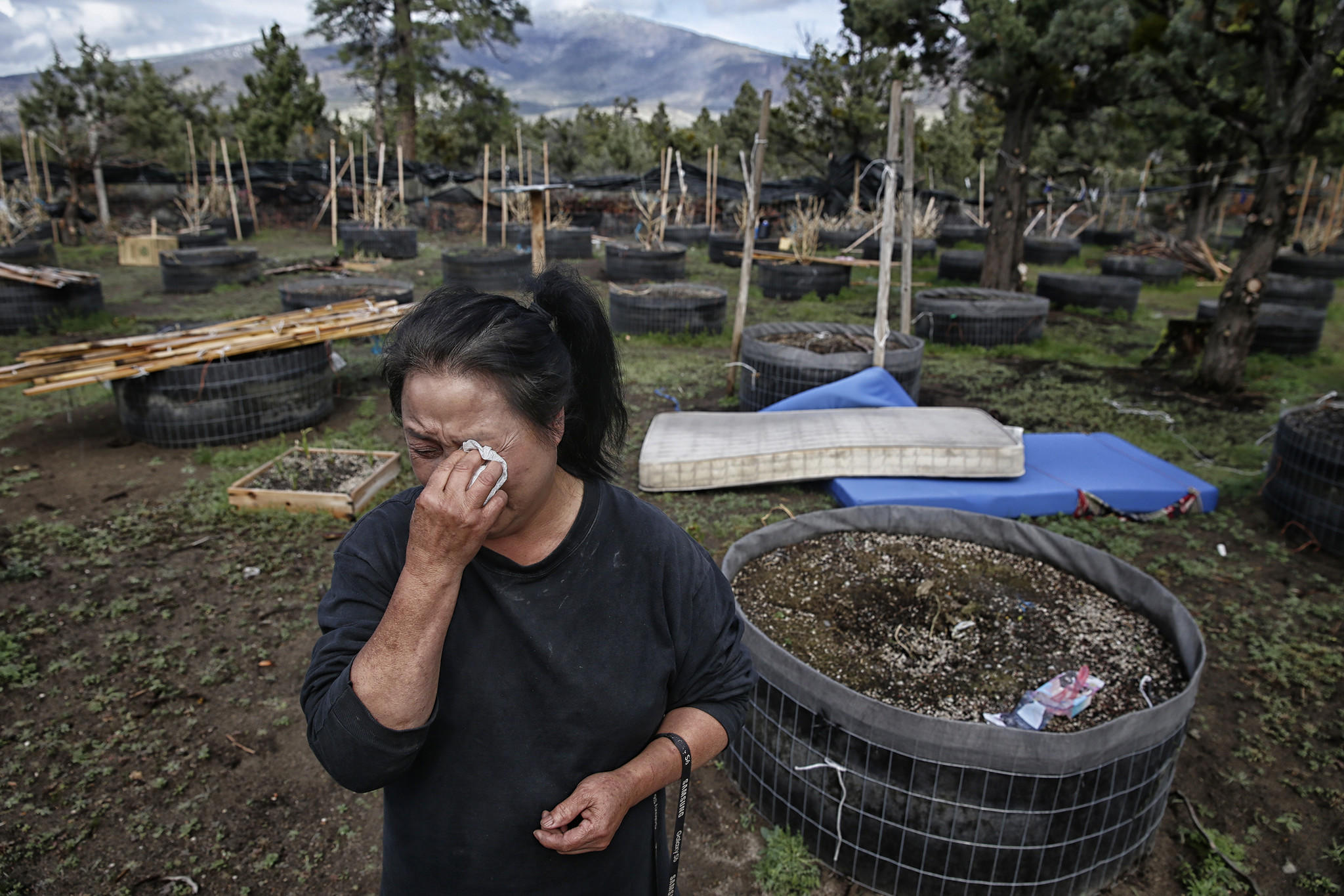 Bao Kelly Xiong weeps as she clears the belongings of her sister, Mee Xiong, from her Mt. Shasta Vista property. Mee died of asphyxiation last winter when she used charcoal in a pot to heat a small enclosure she bedded down in at night.