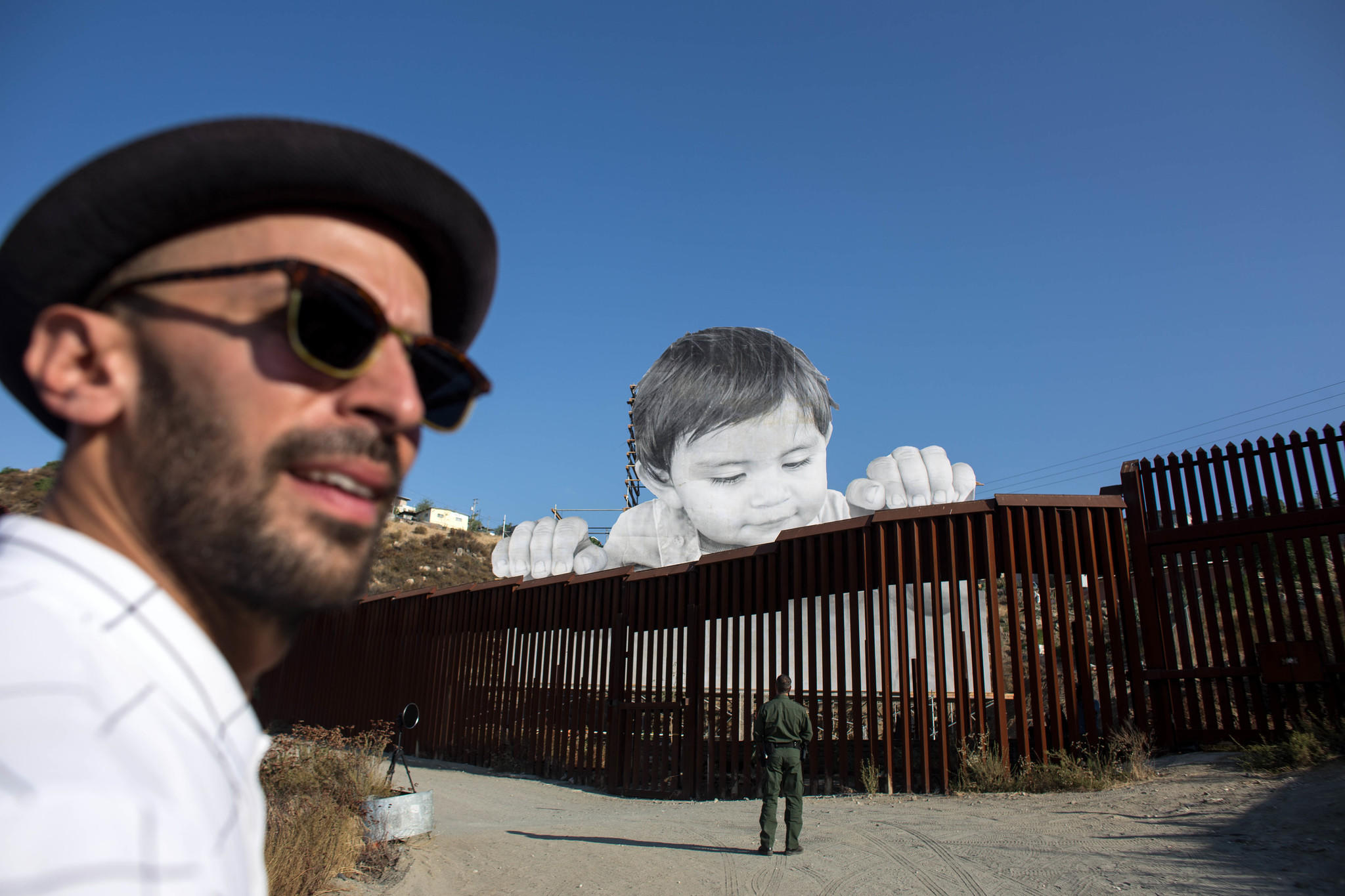 French artist JR, pictured near his artwork on the U.S.-Mexico border in Tecate, Calif., will be speaking about immigration Thursday in Los Angeles. (Guillermo Arias / AFP/Getty Images)