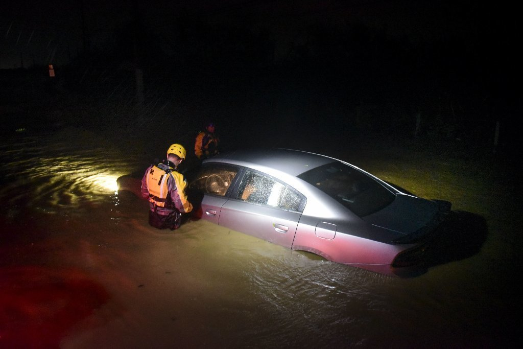 Rescue staff from the Municipal Emergency Management Agency investigate an empty flooded car during the passage of Hurricane Irma through the northeastern part of the island in Fajardo, Puerto Rico, Wednesday, Sept. 6, 2017.