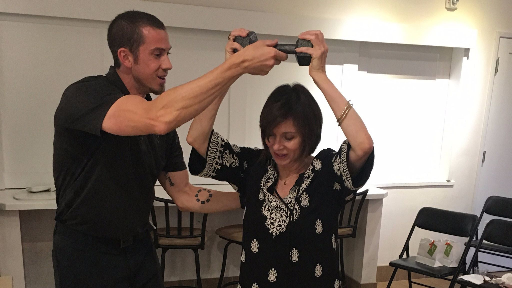 A Reneu Health staffer shows Mari Perez how to raise a weight for improved posture