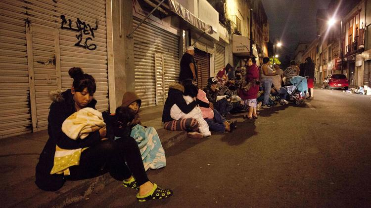 People gather on a street in downtown Mexico City after an earthquake on Thursday.