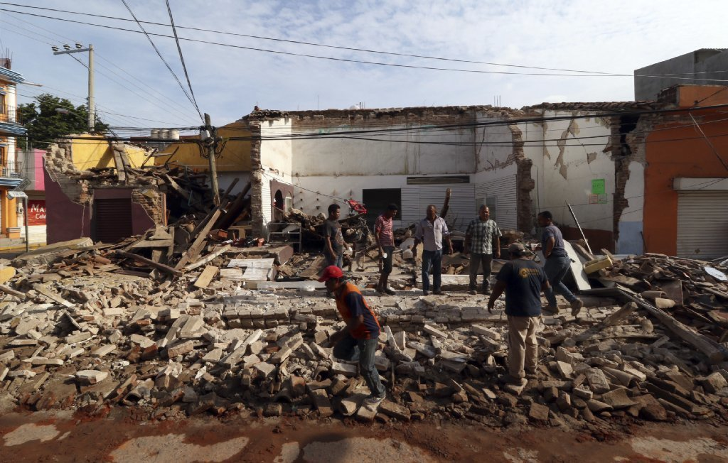 Residents stand on debris of a partially collapsed building felled by a massive earthquake in Juchitan, Oaxaca state, Mexico, Friday, Sept. 8, 2017.