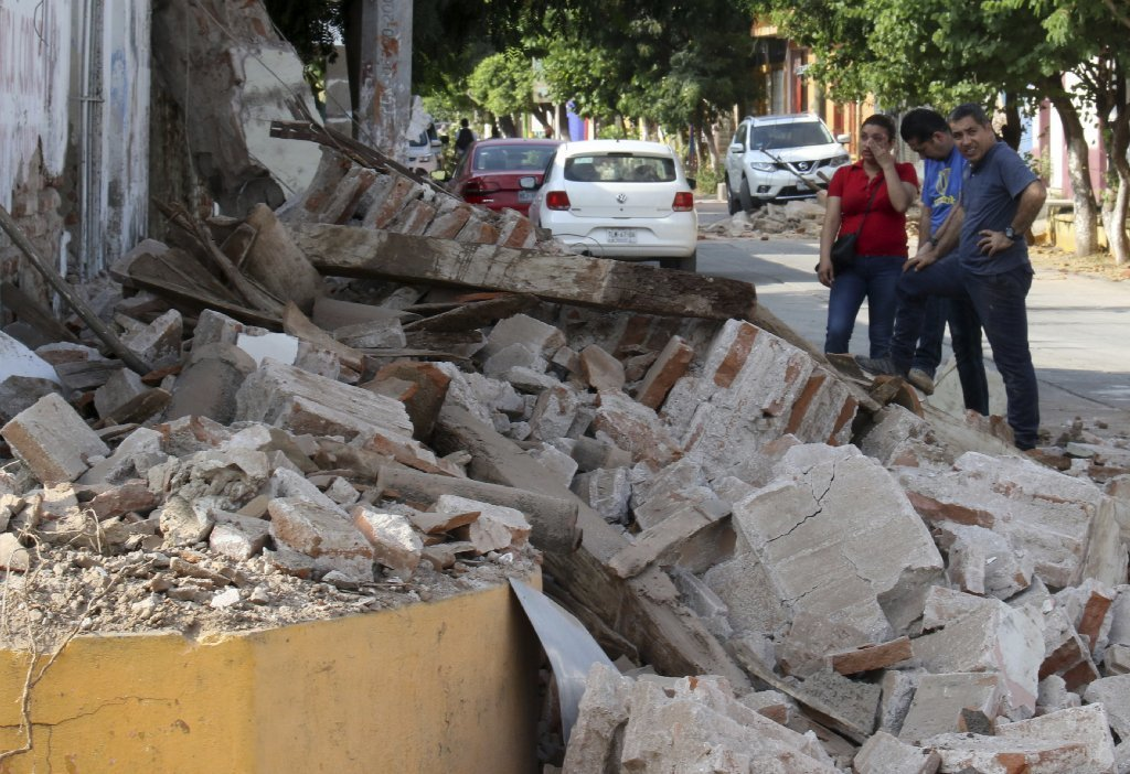 Residents stand in front of rubble from a partially collapsed building felled by a massive earthquake in Juchitan, Oaxaca state, Mexico, Friday, Sept. 8, 2017.