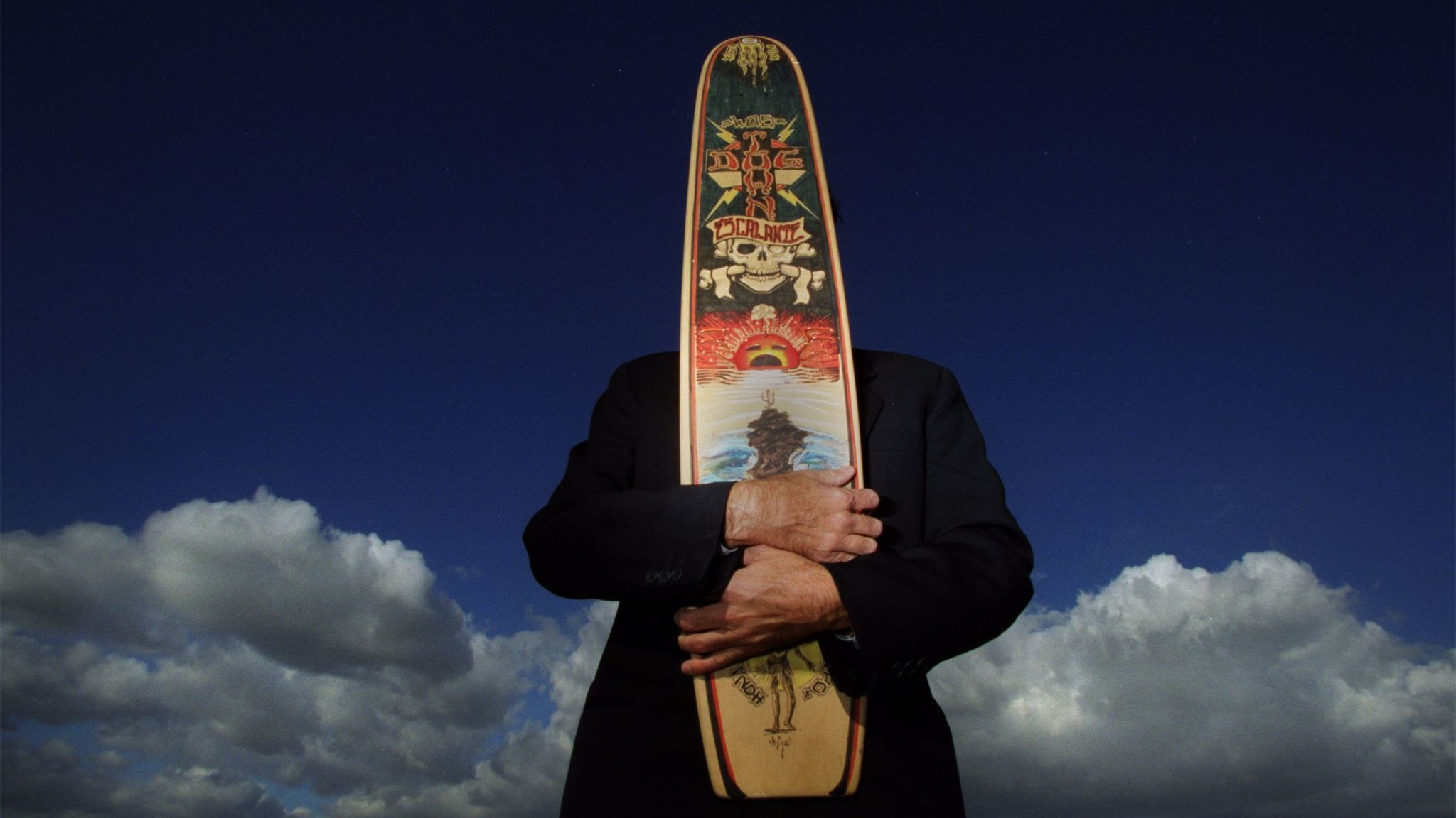 Greg Escalante holds a painted skateboard by artist Kevin Ancell in 2001.