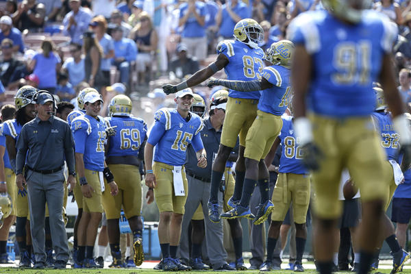 UCLA coach Jim Mora looks on as receiver Alex Van Dyke (83) chest bumps teammate Demetric Felton after his second-quarter touchdown against Hawaii at the Rose Bowl. (Robert Gauthier / Los Angeles Times)
