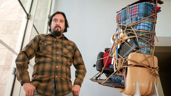 """Camilo Ontiveros stands before """"Temporary Storage,"""" made from the belongings of a DACA deportee, on display at LACMA."""