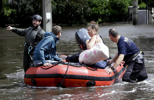 Rescue workers help a couple evacuate their home after it was flooded by Tropical Storm Irma in Jacksonville, Fla. (John Raoux / Associated Press)