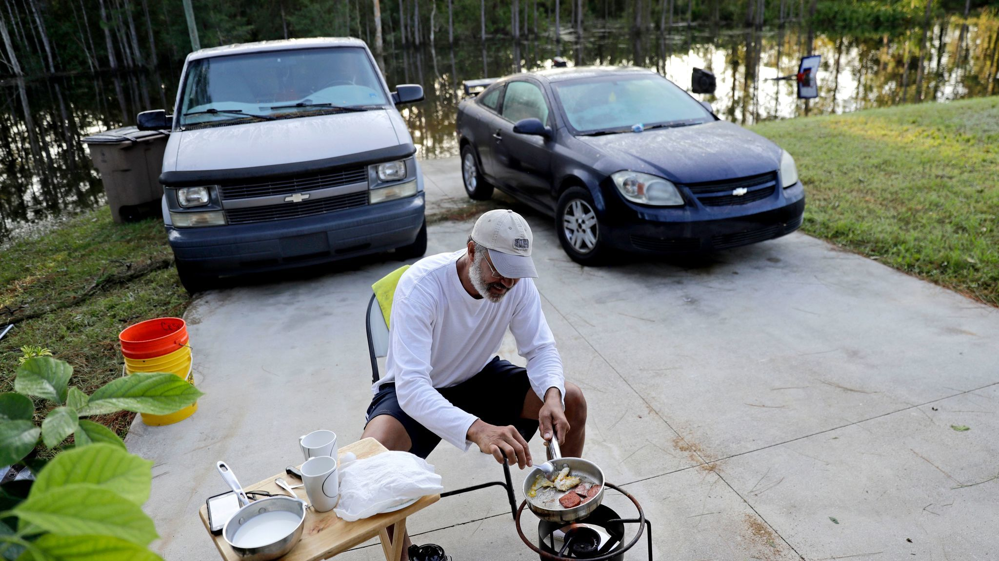 With his Fort Myers, Fla., neighborhood flooded, Cesar De La Cruz makes breakfast Sept. 12 on a propane stove in his driveway.