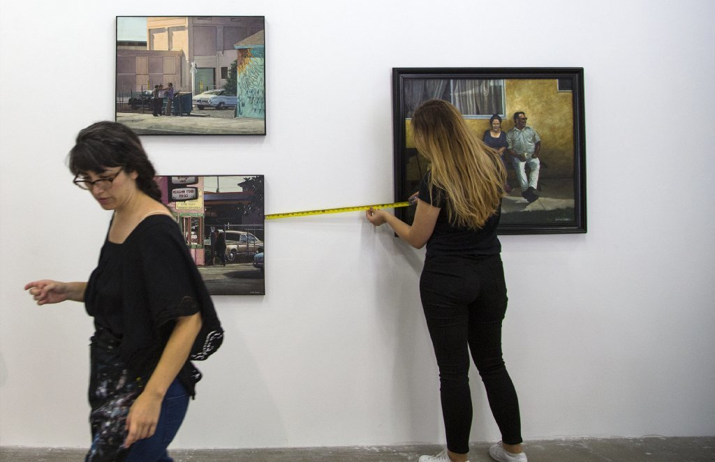 Co-curator Natalie Lawler, left, and student art collection assistant Manon Wogan prepare the university's gallery with oil paintings by the late artist Emigdio Vasquez.