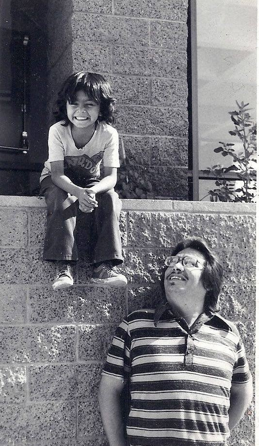 """7-year-old Emigdio """"Higgy"""" Vasquez with his father, the late artist Emigdio Vasquez, in 1975 at Chapman University's Waltmar Theatre. Higgy Vasquez is currently in the process of painting a new mural on one of the building's exterior walls."""