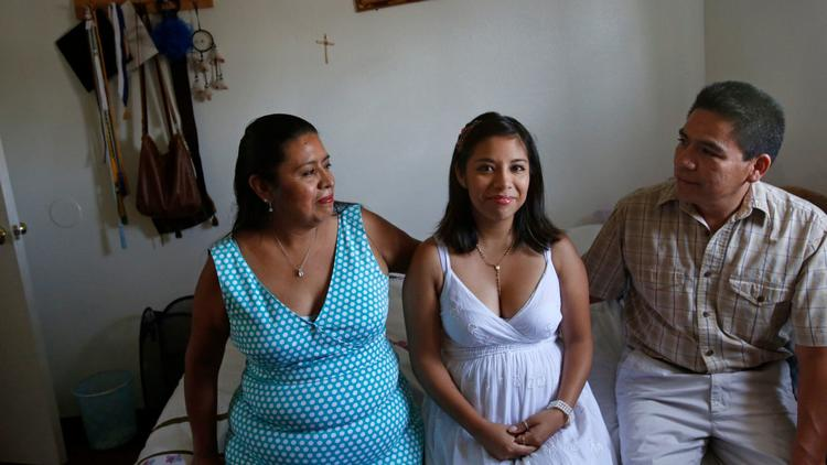Karla Estrada, with her parents Gloria and Angel in their apartment in Chino.