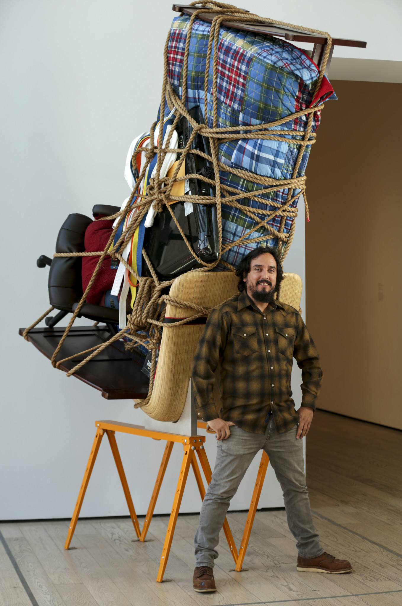 "Artist Camilo Ontiveros stands before ""Temporary Storage: The Belongings of Juan Manuel Montes"" at LACMA."