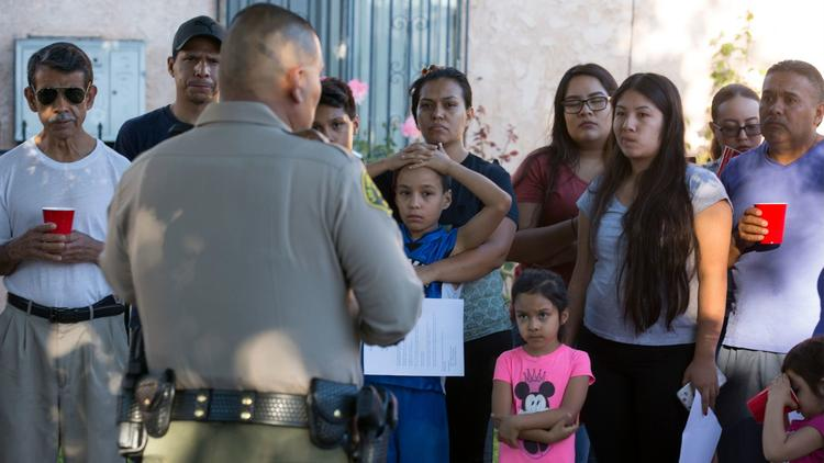 Sheriff's deputy Marino Gonzalez talks with community members during a block meeting in Cudahy.