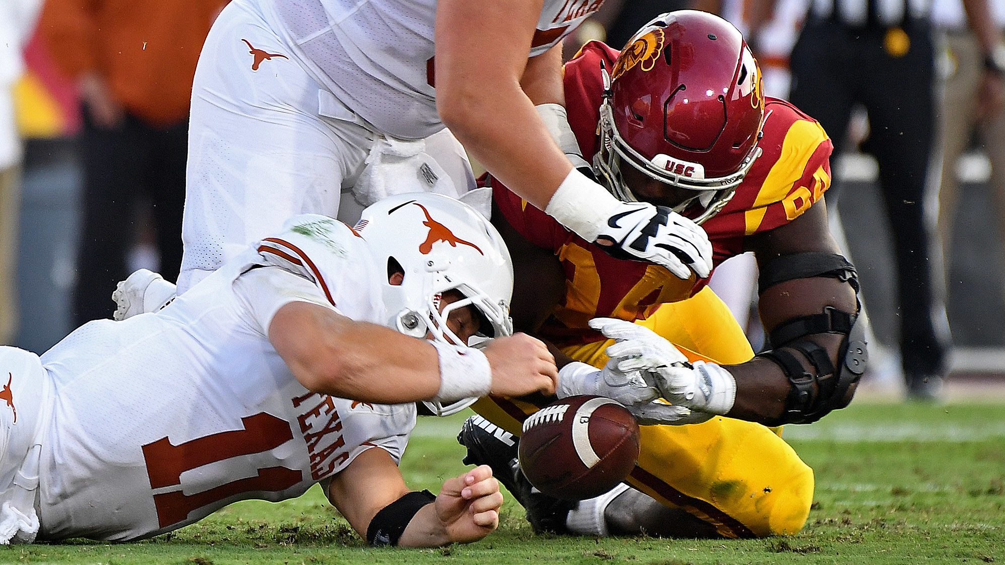 Texas quarterback Sam Ehlinger fumbles the ball in front of USC defensive lineman Rasheem Green during the first quarter of a game at the Coliseum. The Trojans recovered the ball. (Wally Skalij / Los Angeles Times)