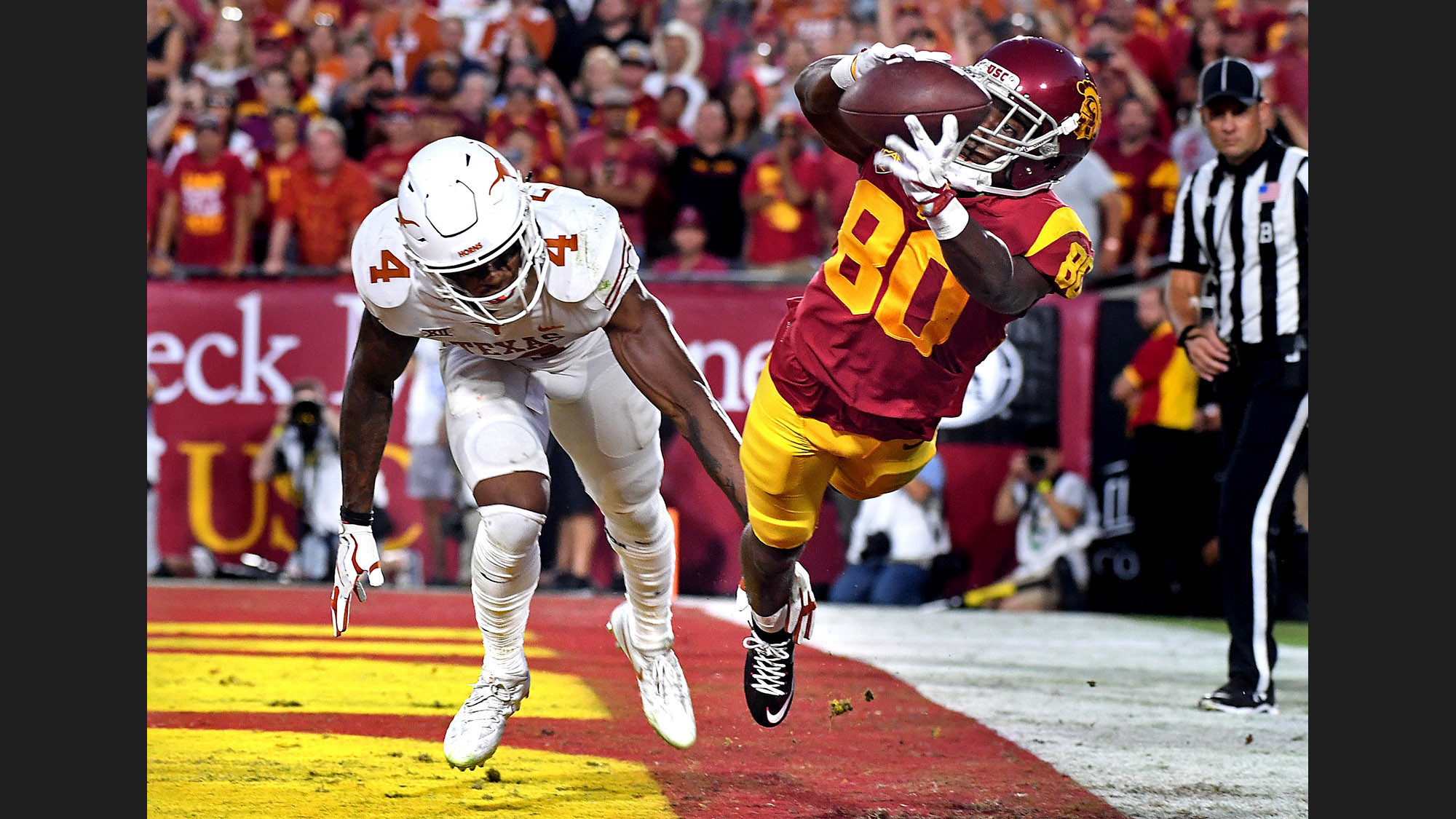 USC receiver Deontay Burnett catches a touchdown pass in front of Texas defensive back DeShon Elliott during the second quarter of a game at the Coliseum. (Wally Skalij / Los Angeles Times)