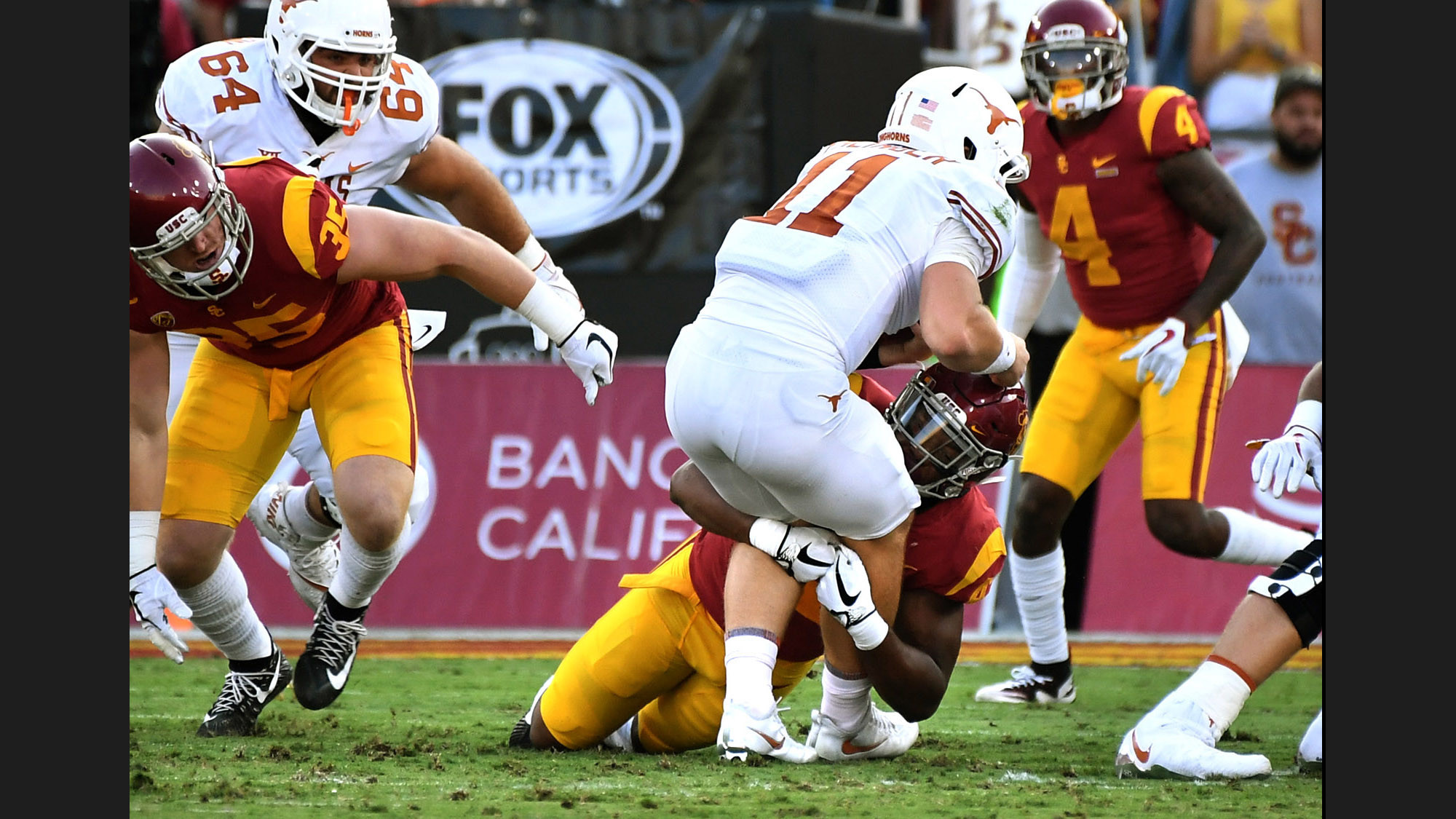USC linebacker Uchenna Nwosu stops Texas quarterback Sam Ehlinger on fourth down during the first quarter of a game at the Coliseum. (Wally Skalij / Los Angeles Times)
