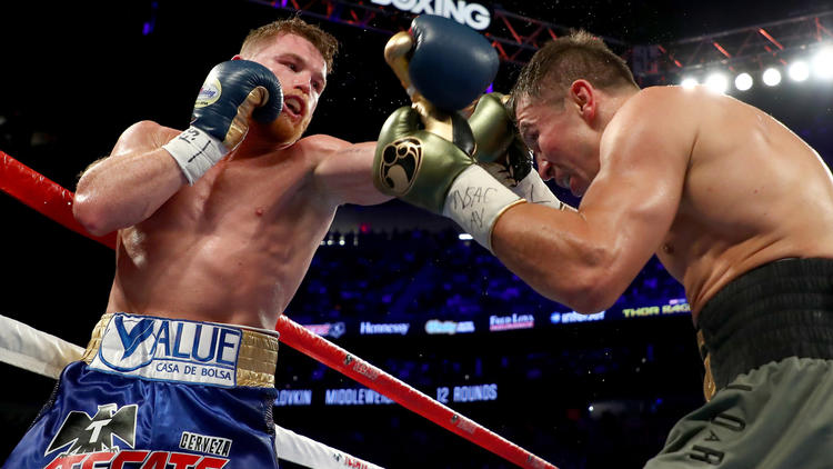 Gennady Golovkin, right, tries to evade a punch by Canelo Alvarez during their middleweight championionship bout. To see more images from the fight, click on the photo. (Al Bello / Getty Images)